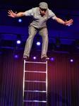 Mann balanciert auf einer Leiter